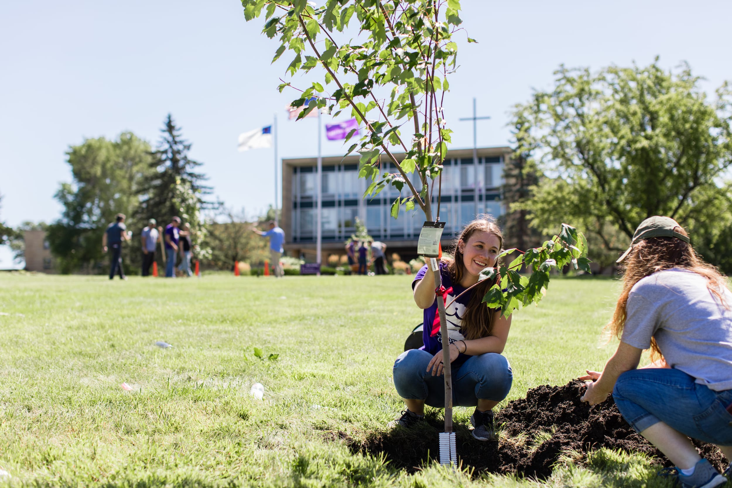 femal students grow a tree in crown college campus