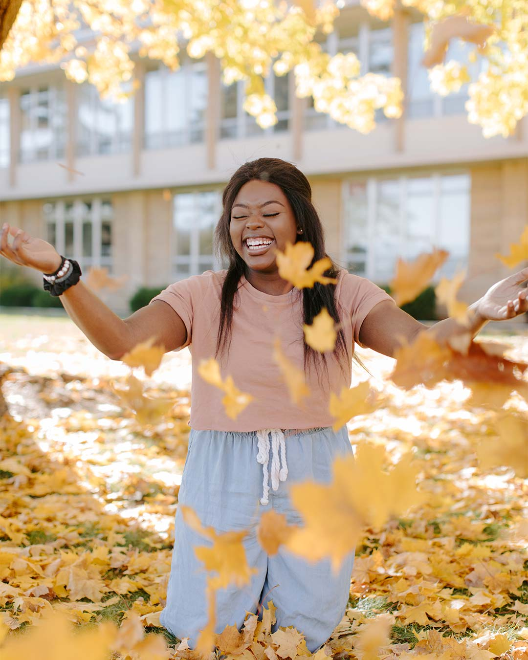 female student smiling among fall leaves in crown college campus