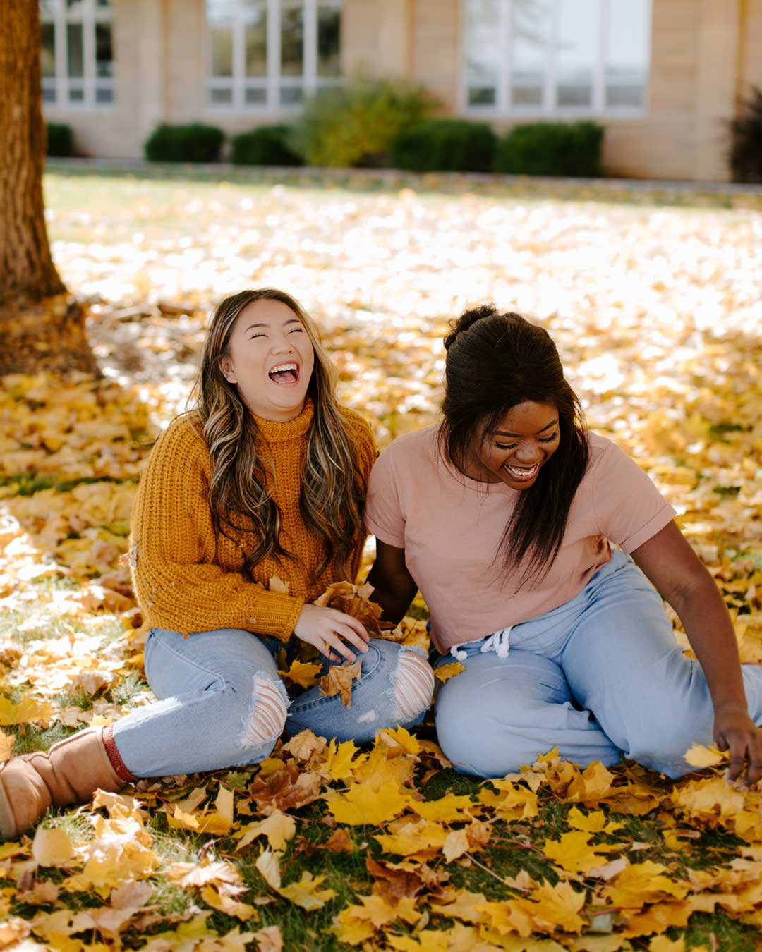 female students enjoying fall leaves in crown college campus