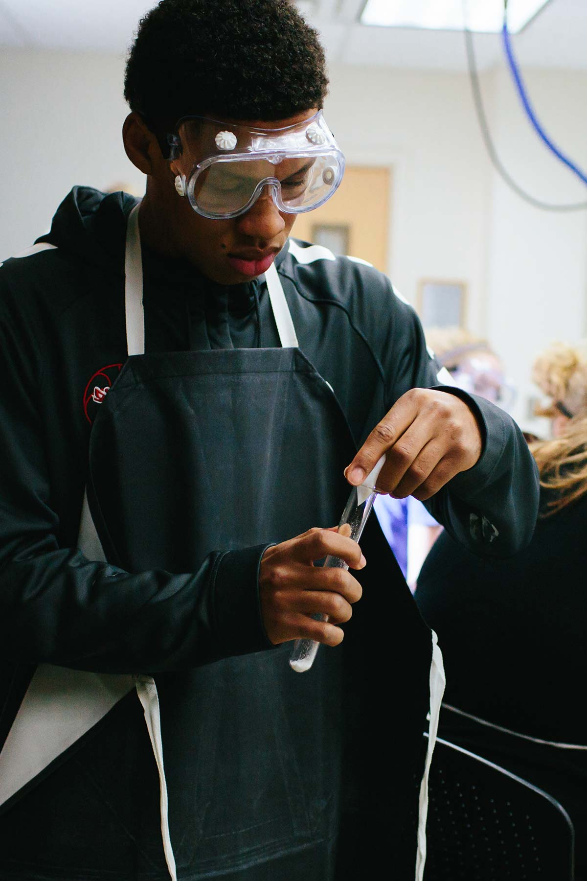 male student doing experiment for christian college degrees