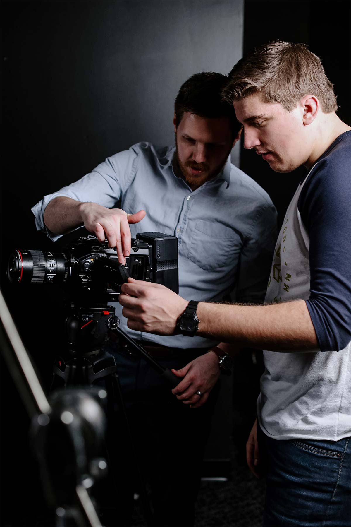 professor showing student professional camera in video production degree
