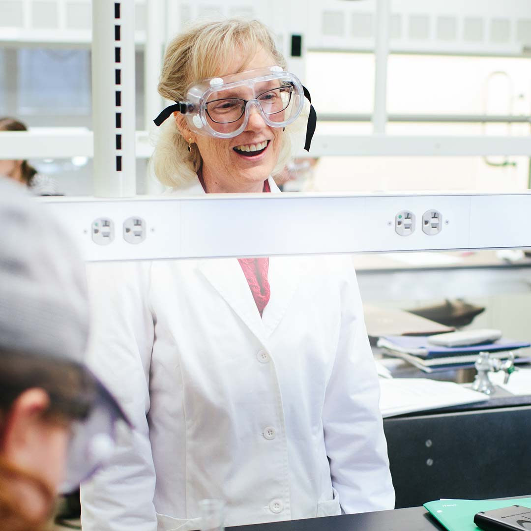 professor smiling in science clothes colleges with teaching majors