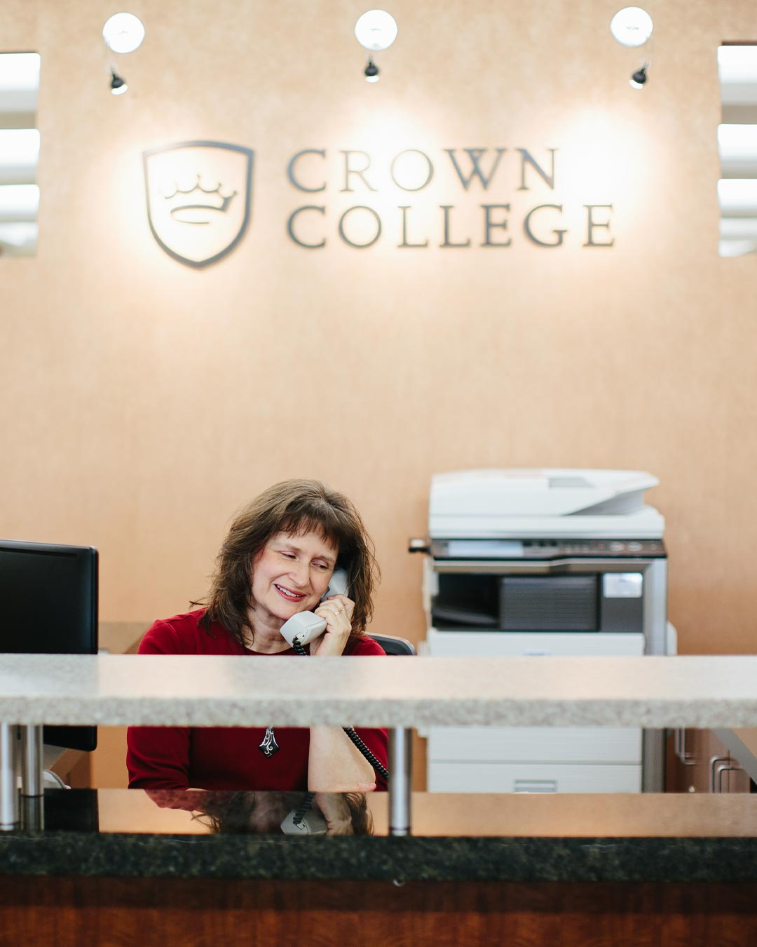 receptionist answering phone crown college admissions