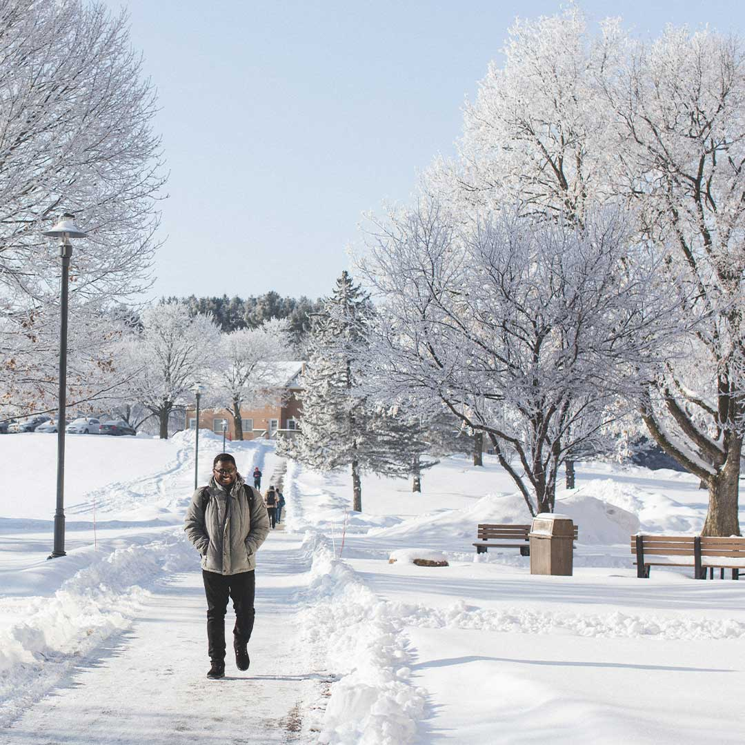 student walking out in snow in crown college