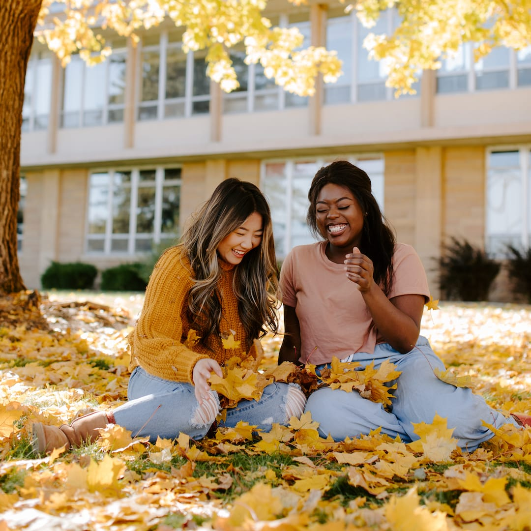 two females under tree in fall in crown college campus