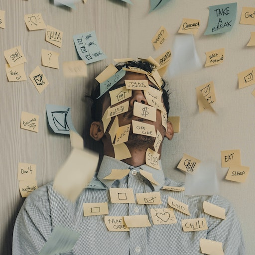 A man leaning in the corner with notes taped all around him, the man is stressed