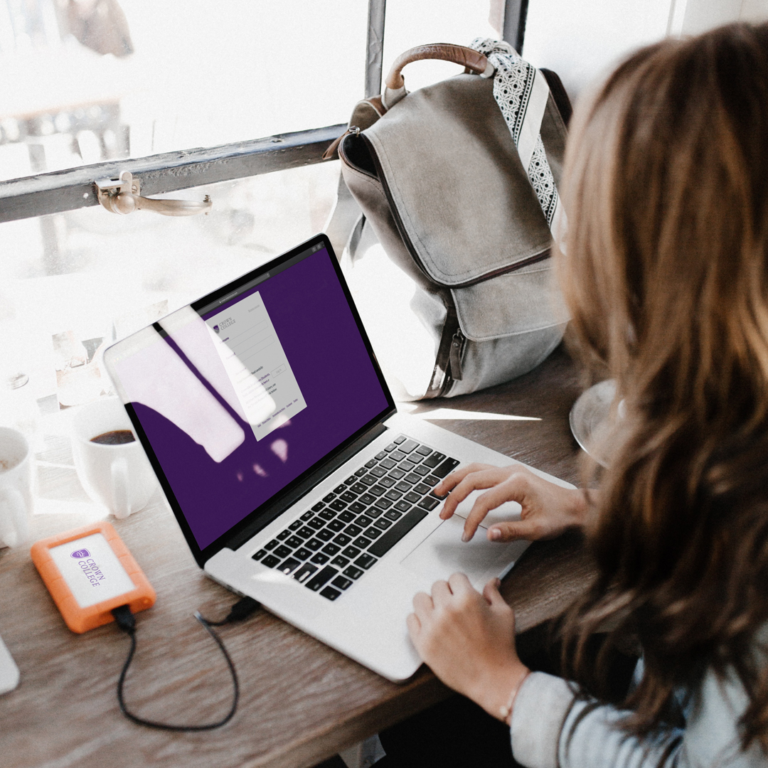 female student looking at laptop for online christian masters degree