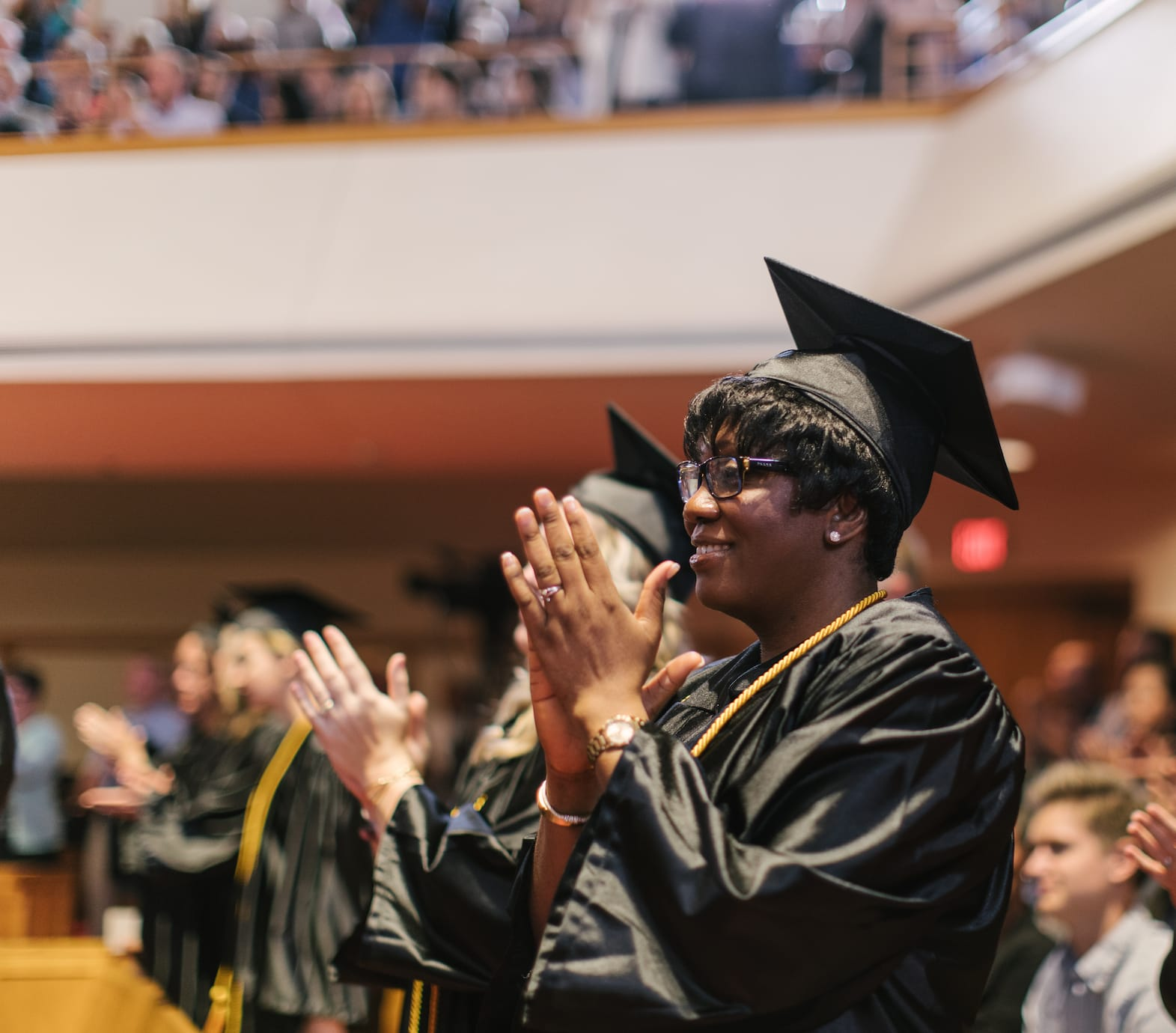 female graduating in crowd clapping of online christian college