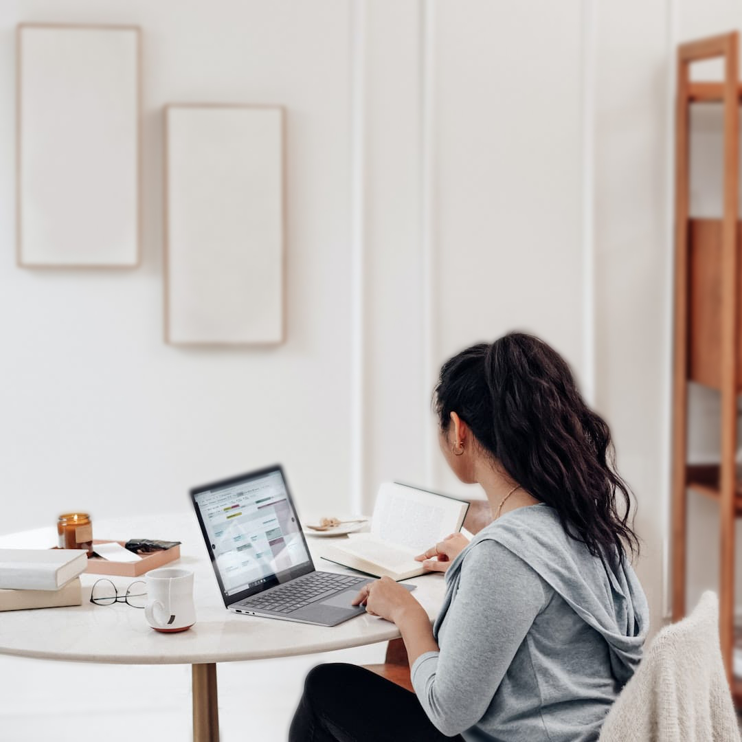female sitting in modern room working on computer blurred for online christian masters degree