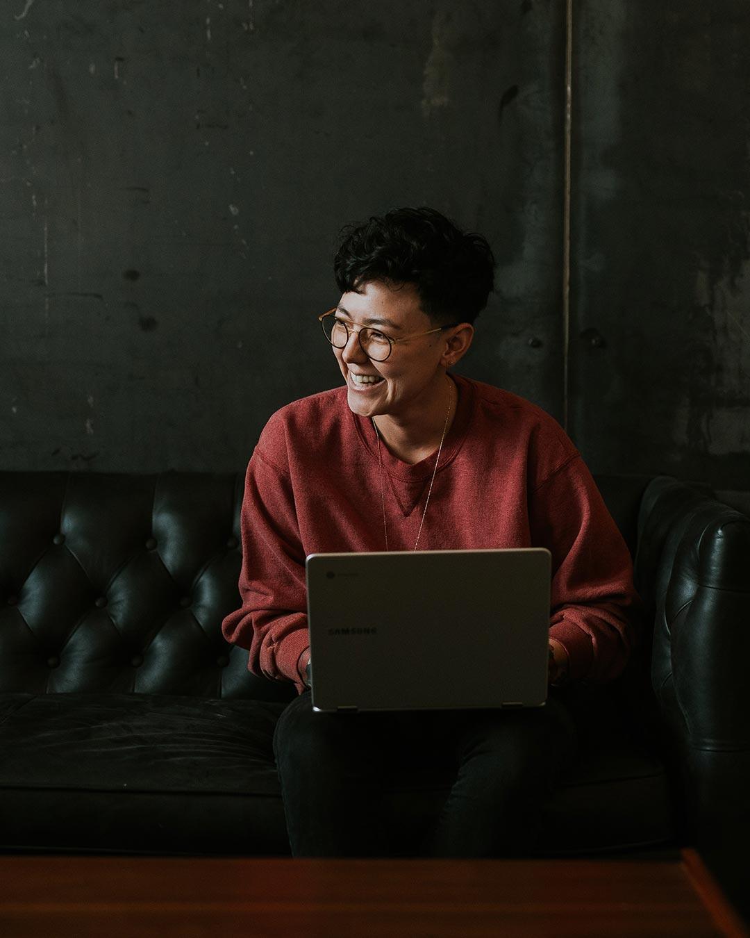 smiling student on laptop online christian ministry degree