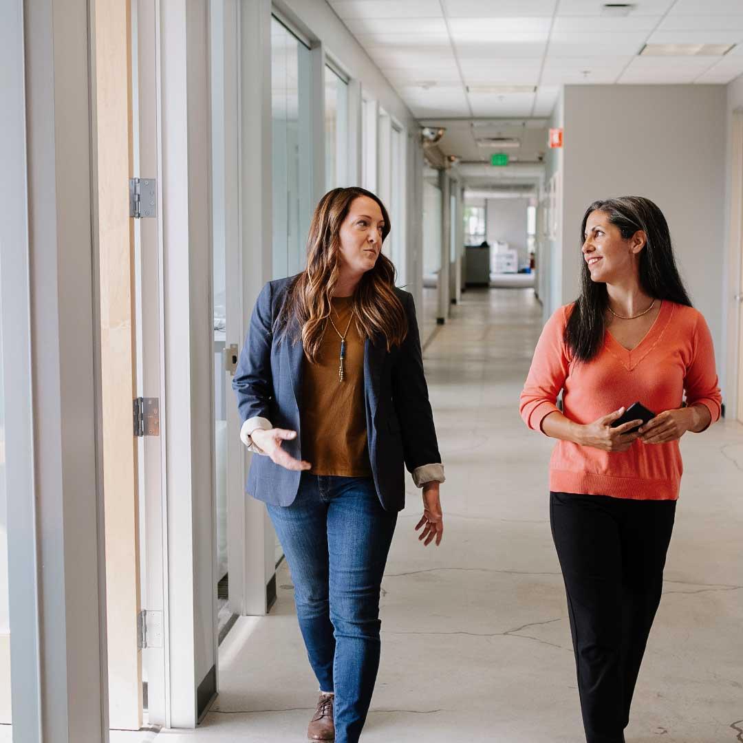women walking lobby college online degree programs