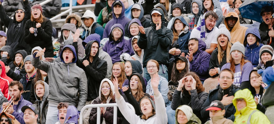fans cheering in stands at stadium in crown college