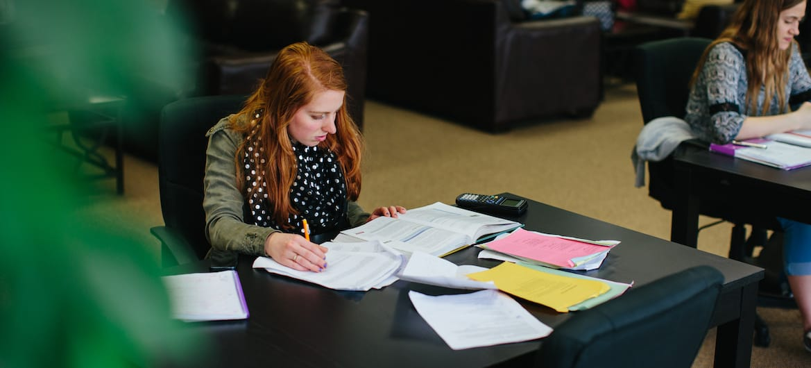 women sits studying in library private christian college